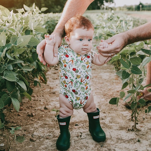 Little Cache wearing the best-selling Veggie Garden Onesie.