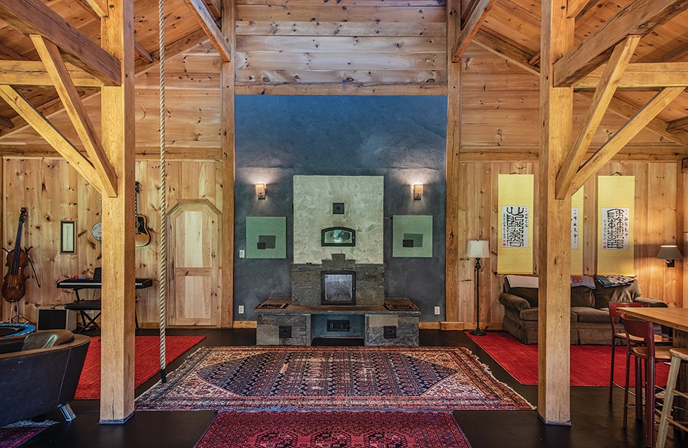 The home's large main room—with dining and living areas and the kitchen—strikes a balance between family and contemplative space. A trampoline and a climbing rope hung from the ceiling are regularly utilized by Duncan and six-year-old August for exercise, and the space's western corner is dominated by Masse's collection of instruments. In opposing corners, two peaceful sitting areas provide views to the surrounding landscape. Duncan - designed the bluestone fireplace at the room's center. - PHOTO: DEBORAH DEGRAFFENREID