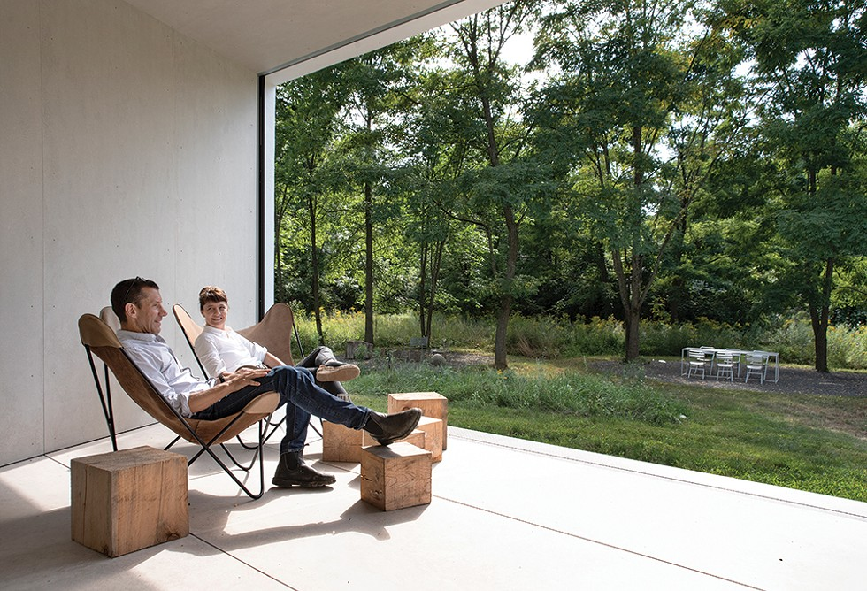 """Stella Betts and David Leven look out at their property's surrounding campsite. The covered porch, which features retractable screen walls, """"is actually one of our favorite rooms in the house,"""" Betts says. """"Our designs are committed to capturing the relationship - between the amazing, the sublime, and domestic space through the interplay of elements and crossing boundaries between inside and outside,"""" Leven adds. - PHOTO: DEBORAH DEGRAFFENREID"""