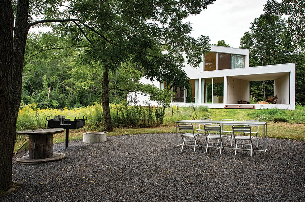"""Looking back at the house from the outdoor kitchen and dining area. With multiple doors throughout the house allowing access between the landscape and the home's interior, the couple and their guests use the - home and campsite features interchangeably during the warmer months. """"There's an interplay of elements within the wrapper of the house,"""" explains Leven, """"but also within the wrapper of the landscape and sky, and - even within the wrapper of the Hudson Valley."""" - PHOTO: DEBORAH DEGRAFFENREID"""