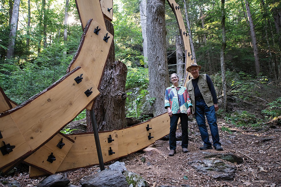 Artists Laura and Rick Brown stand before - Dreaming, which was created by connecting lumber from a storm-downed hemlock to a living ash tree. - PHOTO: KARI GIORDANO