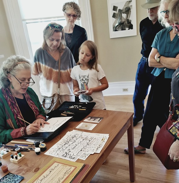Elinor Aishah Holland demonstrates calligraphy during ArtWalk.