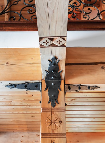 """""""It's kind-of a lost art form,"""" explains Laroux of the detailed, Zakopane wood carvings etched along beams and in corners of the house. The carvings feature various motifs inspired by life in the Tatra mountains. """"There are a lot of little details everywhere,"""" he says. """"When you sit long enough, you begin to notice."""" - PHOTO BY DEBORAH DEGRAFFENREID"""