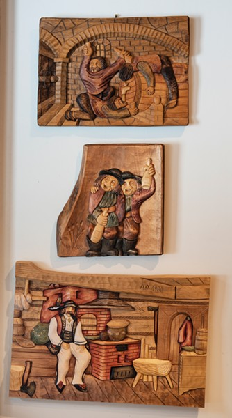 """A traditional woodcarving from Podhale hangs in - the home's basement bar and entertaining space. In traditional Polish style, the family has enjoyed sharing the home with friends. """"He was a very strict, hardworking guy, but he also loved to entertain and party,"""" says Jack Laroux of his father, who didn't like to brag. """"He was a very humble guy. He was proud of [the house] but he'd never say anything. When people would ask, he would just say, 'Yeah, I built it.'"""" - PHOTO BY DEBORAH DEGRAFFENREID"""