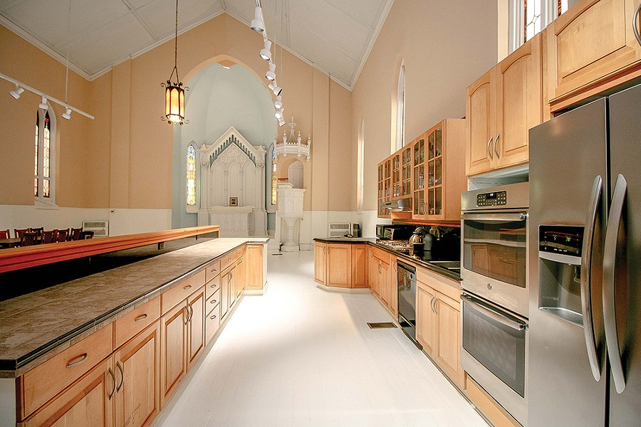"""Previous owners added a full kitchen and an island to partially divide it from the former church nave. However, the open space appealed to Bokaer's aesthetic. """"Loft living is dear to me,"""" he says. """"You can trace that aesthetic here to the open plan and the clean, streamlined, minimal design."""" - PHOTO BY SETH DAVIS"""