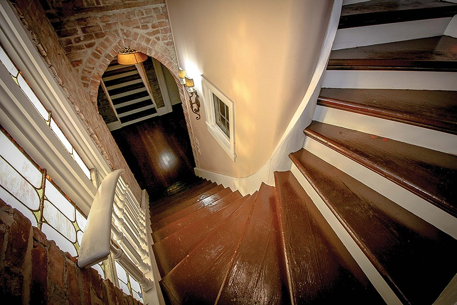 A winding staircase leads from the entryway to the lofted bedroom. Bokaer has kept the minimalist aesthetic throughout the home, letting the stained glass, exposed brick, wood trim, and architectural flourishes take the spotlight. - PHOTO BY SETH DAVIS