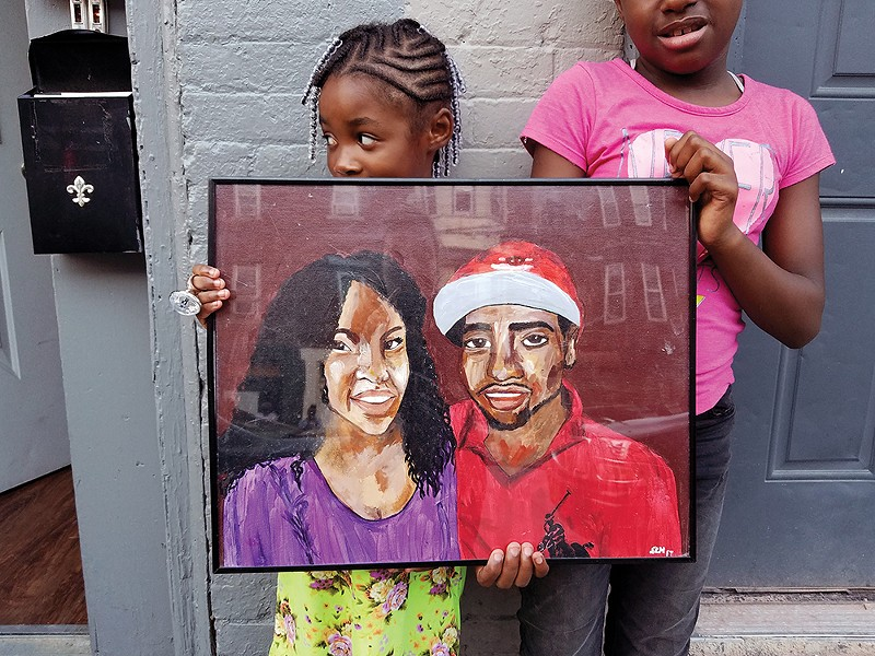 Relatives hold a painting of Gevontay Owens-Grant, who was killed at a Valentine's party at 253 South William Street in Newburgh in February 2017. He's pictured beside his fiancée, Demira Melvin. - PHOTO BY LAUREN BERG