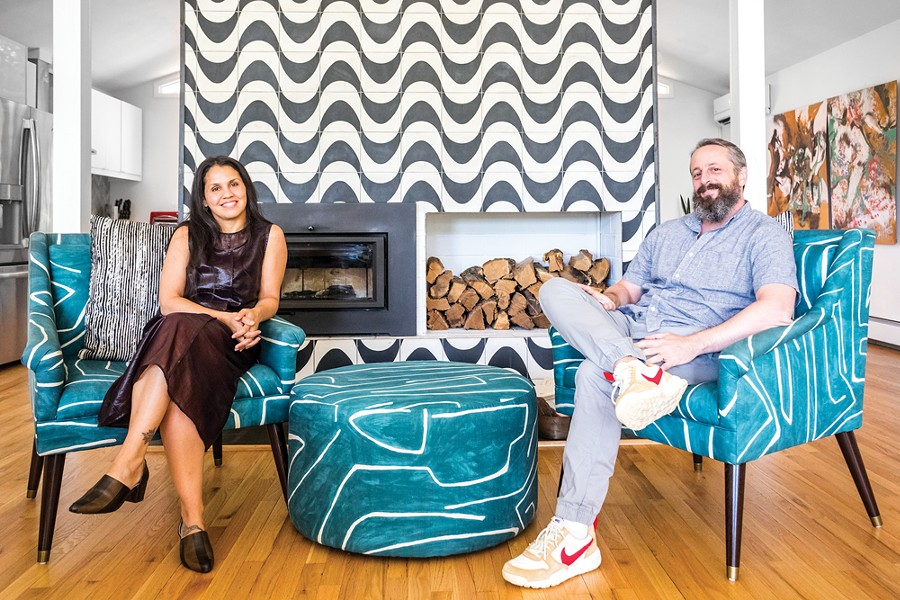 Ana Claudia Schultz and Aaron Smyle in - their open-concept living room. By removing stone - wing walls from the fireplace, they opened the - space to the adjacent kitchen and dining area. The - blue-and-white chairs are made of fabric designed - by Kelly Wearstler—Schultz sourced the same - fabric and then commissioned a matching ottoman - from her upholsterer. The abstract painting in the - dining room is by Ryan Wheelbarrow. - PHOTO BY WINONA BARTON-BALLENTINE