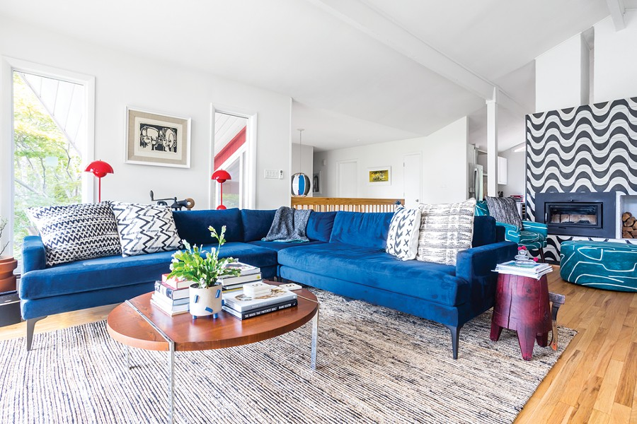 "A lounge in the living room was carefully planned to take full advantage of the river - views and then decorated with an eclectic mix of colors and textures. ""I'm always - trying to throw curveballs,"" says Schultz about her design ethos. ""I look for the - dynamic between people and then figure out ways to implement their particular - character into their family areas."" The block print featured on the wall is a particular - favorite. Titled Two Little Boys, it was created by civil rights lawyer R. Livingston. - PHOTO BY WINONA BARTON-BALLENTINE"