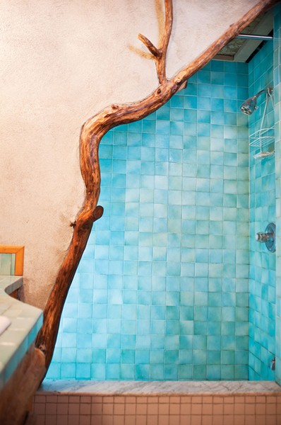 "The downstairs shower made of blue tile and branches. ""We tried to bring into the house as many of the materials that grow on the land as possible."" - DEBORAH DEGRAFFENREID"