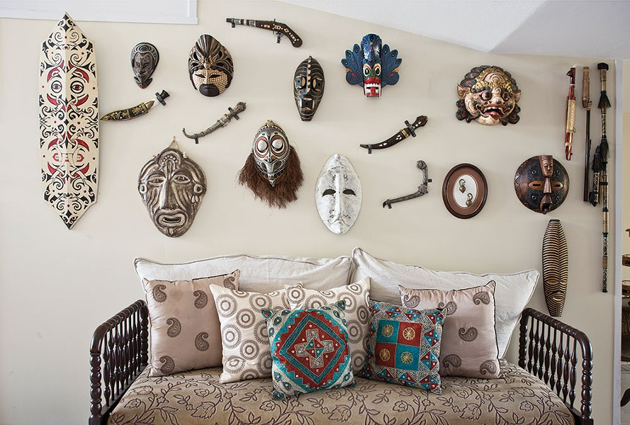 "A wall of masks and weaponry collected during Narine's travels. Through her travels, Narine has become adept at thinking on her feet and adapting to whatever culture she's in. ""When you travel you are constantly discovering new things about yourself, your strengths, your motivations, and what really inspires you,"" she says. - DEBORAH DEGRAFFENREID"