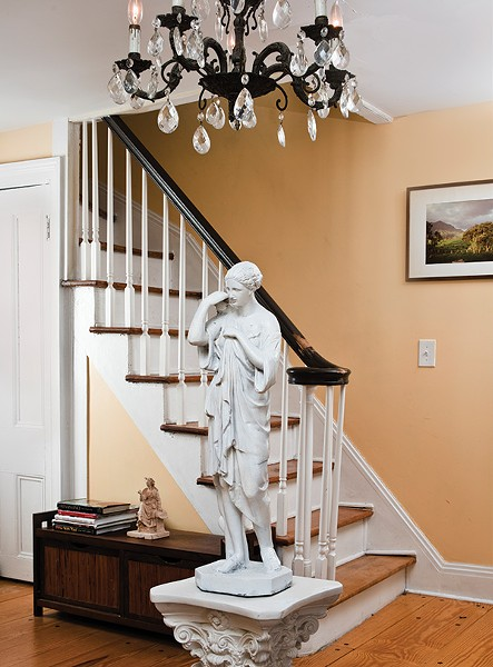 "The home's foyer dates from the 19th century and has low ceilings. ""The chandeliers came with the house,"" Palaia explains. An antique statue depicting a Roman woman was collected by D'Ambra. Placed under the chandelier, it keeps guests from hitting their heads."