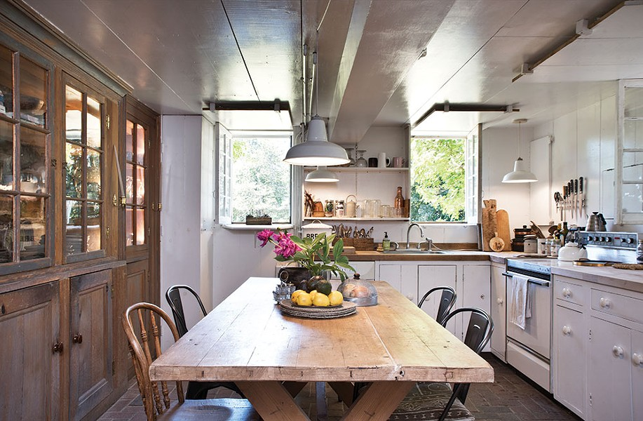 The couple found a 19th-century Swedish farm table for the downstairs kitchen and Doornbos restored the wood counters. The glass hutch is original to the house. - DEBORAH DEGRAFFENREID