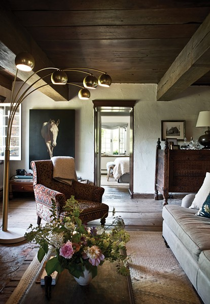 An eclectic blend of 20th-century pieces fill the home's living room to create a space that's both elegant and comfortable. A mid-century Italian brass floor lamp faces an Indian wedding chest in the corner of the room. A mix of sofa and chairs face the original brick fireplace, carefully repaired by a local stone mason and now in working order - DEBORAH DEGRAFFENREID