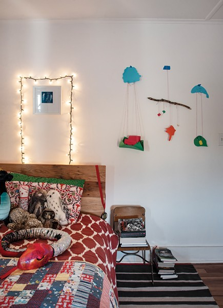 Their older son's bedroom features his parents' handiwork. Szlasa made the headboard from reclaimed wood and Rodabaugh stitched the quilt as well as the hanging mobile.