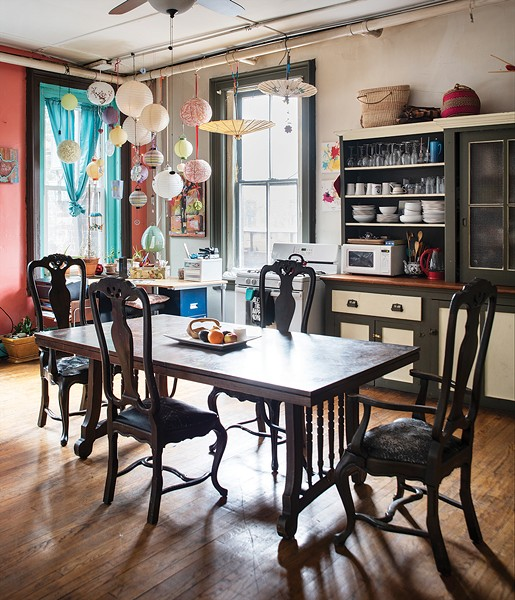 The loft's main kitchen looks over the backyards over the neighboring buildings. Bickman painted the wall and trim a contrasting orange and blue, but left the original sideboard grey and yellow. Over the desk, she camouflaged some unsightly pipes with hanging lanterns and mementos. - PHOTO BY DEBORAH DEGRAFFENREID