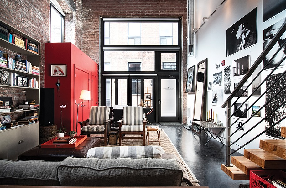 The front end of the loft is dominated by a bright red closet Rice added when she moved in. The striped grey chairs were upholstered with fabric from Sylvester & Co. in Sag Harbor, NY and paired with a cowhide bench made by Amy Pilkington. The marble coffee table in the foyer is from Maison Gerard in New York. - PHOTO: DEBORAH DEGRAFFENREID