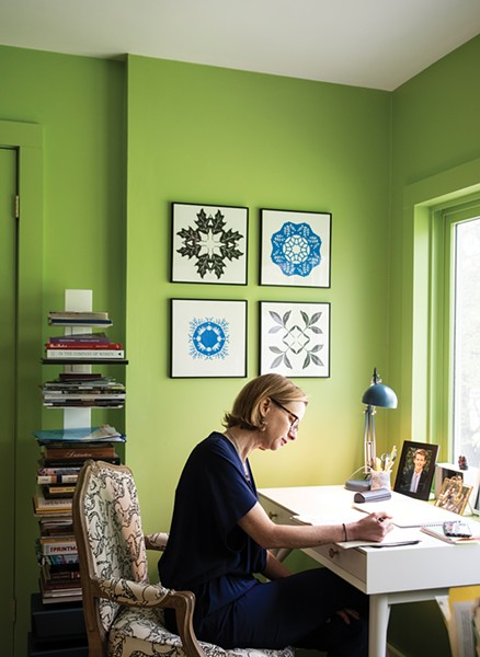 "Walker sitting at her desk. The geometric paper cuttings hung above are also by local artist Jenny Lee Fowler. ""A lot of what I do is help people find their own style and inspire them to be more confident with their own design decisions,"" explains Walker. ""Every job is completely new. It has to do with that person, their space, and who they are. I love collaborating and find myself appreciating someone else's idea that at first I might have disagreed with. That's the fun part."" - PHOTO: DEBORAH DEGRAFFENREID"