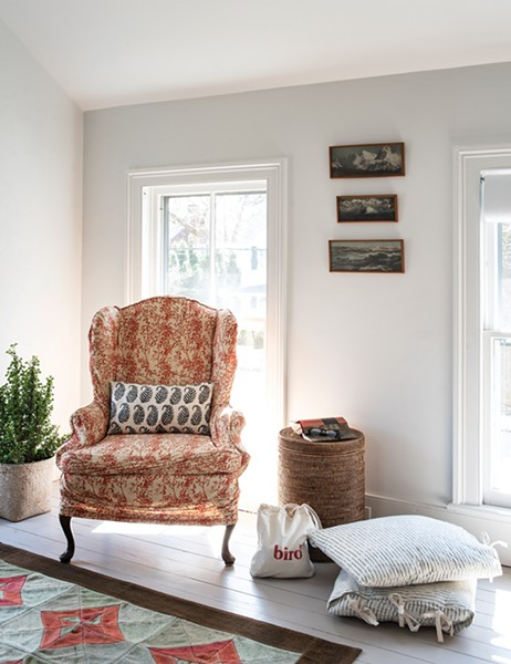 "A sitting area makes up a cozy corner of the - home's master bedroom. ""I love pattern, and I've always collected textiles,"" she explains. She bought the triptych photo of a mountain range hung above the chair from a thrift store in Brooklyn. - PHOTO: DEBORAH DEGRAFFENREID"
