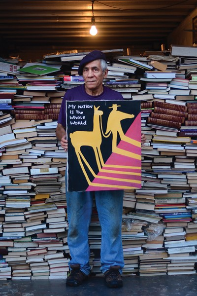 Martin Muñoz with one of his paintings and part of his book collection. - PHOTO: OTTO OHLE