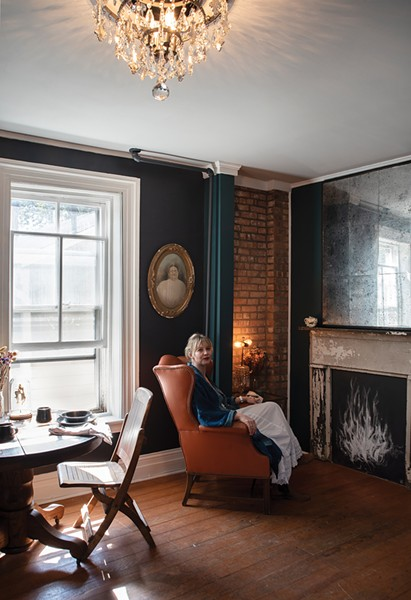 """Brooke Nelson, Transformative Spacing. Nelson reposes in the showhouse's second-floor kitchenette. """"[It's] a high traffic area used by four AirBnB guest rooms,"""" she explains. """"I had to create a space that gives guests an experience that stands out."""" Her self-described """"whimsical steampunk"""" style often combines antiques with offbeat art, colors, and decor. Inspired by her interior designer mother, she often searches the local landscape for ideas. For this striking look, she used the Historic Cornell building on the Kingston waterfront as inspiration.""""I love the rust colors of the metal against the brick,"""" she says. The kitchenette borrows the metallic color scheme and contrasts it with the use of crystal, metal, wood, and velvet. - PHOTO: DEBORAH DEGRAFFENREID"""