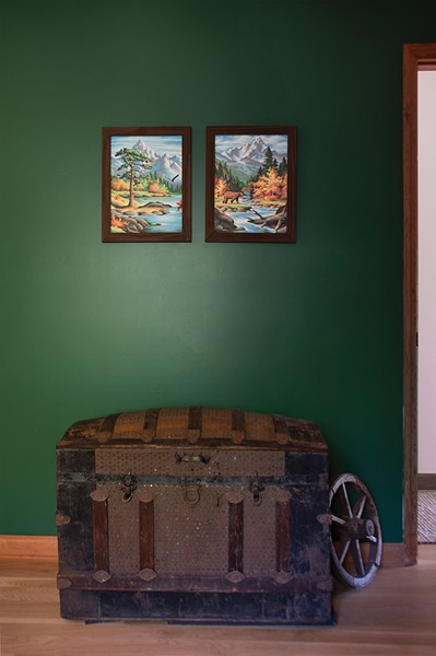 """The couple painted an accent wall in the first-floor guest room to add a pop of green. Originally they'd thought to decorate the home with a """"rustic-modern vibe"""" and collected trunks, weathered crates, and paintings from upstate flea markets. After deciding on a different aesthetic for a majority of the house, they conceded to decorate the guest room with their upstate finds, including an antique trunk, oil paintings, and a collection of maps. - PHOTO: DEBORAH DEGRAFFENREID"""