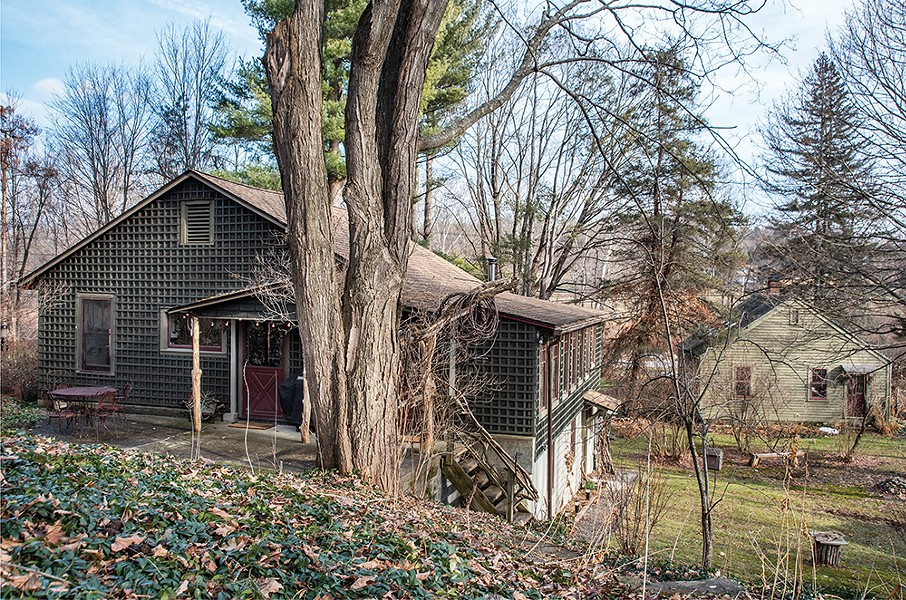 """Feinberg's one-acre property backs into a wooded hillside and was surrounded by slightly - wild but well-planted gardens, which, along with - the buildings, she eventually brought back to life. - """"I'd never gardened until I got here—that was a - revelation,"""" she says. In the foreground, her lattice-covered house looks out onto a private courtyard. - and an exterior staircase with a playful bannister - of twisted branches that Feinberg collected from - the property. - PHOTO: DEBORAH DEGRAFFENREID"""