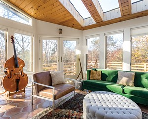 The music room of Sree Kant and Annie Duflo's house is flooded with light. Once a sun porch, the west-facing room enjoys views of the nearby Catskill Mountains and lush winter sunsets. It's the perfect place to practice an instrument—a favorite pastime for both Duflo, who plays the piano, and Kant, who is learning the bass.