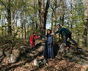 """Chris Mottalini, his wife Nepal Asatthawasi, and their son Nino on a stone outcropping near their house. The 1950 home was originally handbuilt from bluestone harvested from the surrounding land by an Irish stonemason. """"There are stone walls running all through the woods here,"""" says Mottalini."""