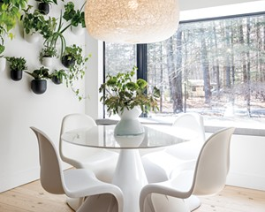 """Sun floods into Oldenburger and Smykowski's kitchen, even on winter days. The thriving wall garden adds layers of green to the beige-on-white design. Oldenburger found two of the Vernor Panton chairs by Vitra at a vintage shop and matched them with a round table and pillar pedestal base. The wall pots and hanging lamp are both by West Elm. """"I do love plants,"""" she says. """"I try to have live plants throughout the house and encourage my clients to also."""""""