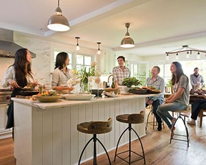 """Betty Choi, chef Doris Choi, Niall Grant, Craig Leonard (from left to right) in the kitchen. (Daughter Maia, seated with them at the island, and their guests will soon enjoy the lunch being prepared.) The Choi sisters have always had strong ties to food and family. Their journey—both to Woodstock and to a better understanding of nutrition—has changed all of their lives. """"Our awareness of food and our relationship to it is now a daily focal point in the way we live,"""" says Leonard."""