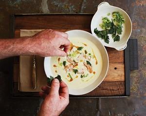 Binnekill Tavern chef Bryan Calvert plating smoked trout soup with crispy parsley.