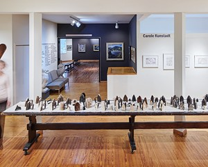 Pressing On installation, 86 antique sad irons on 16' wooden table by Elizabeth M. Fraser (ca. 1920), Woodstock Artists Association & Museum