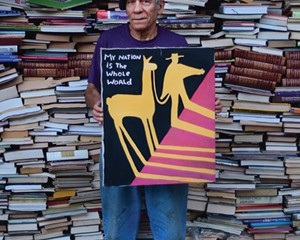 Martin Muñoz with one of his paintings and part of his book collection.