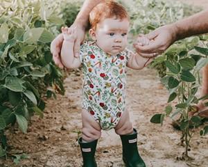 Little Cache wearing the best-selling Veggie Garden Onesie.