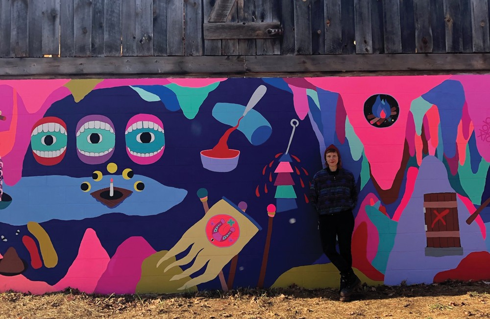 Macon Reed in front of her recently completed mural at Stoneleaf Retreat in Eddyville