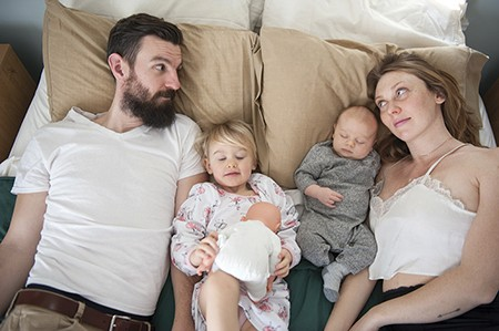 Kyle Needham and Alexis Arvidson Needham in the family bed with Layla and Bowie. - HILLARY HARVEY