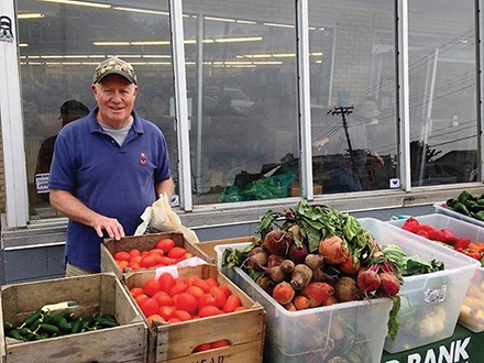John, a volunteer at People's Place, works the front of the line for the Farm Stand every Tuesday.