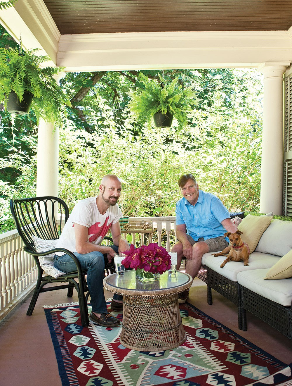 """Douglas Sexton, Danny O'Connell, and their dog Dean on their front porch. """"We're friends with everyone on the street,"""" O'Connell says. Sexton agrees. """"People come over and hang out. It really has become a what we wanted it to be—a gathering spot for friends and family."""" Even the neighbor's chickens regularly come to visit. - DEBORAH DEGRAFFENREID"""