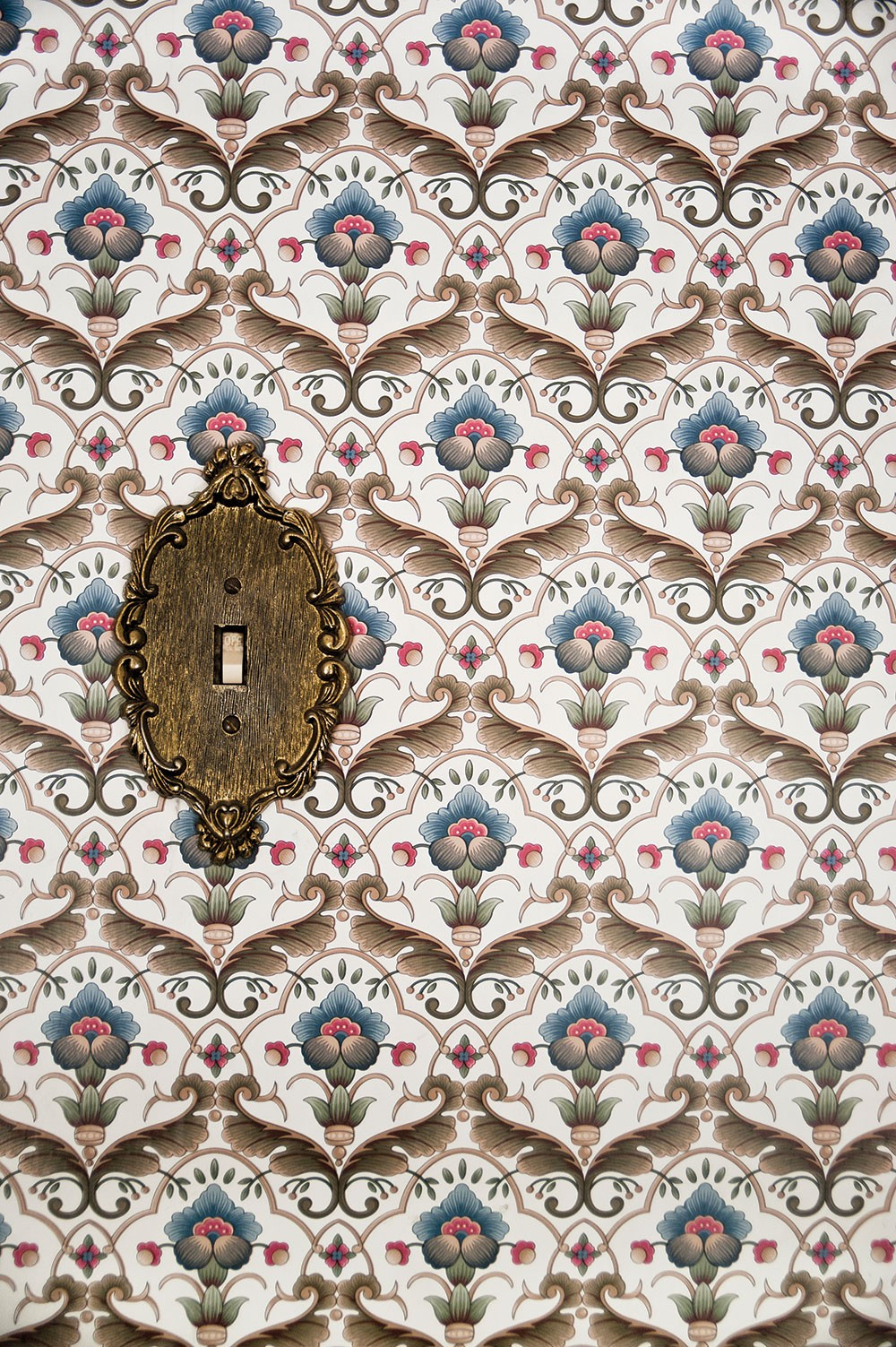 """The couple kept the original wallpaper and light switch panel in the upstairs guest room. """"This is everyone's favorite room to stay,"""" Sexton says. - DEBORAH DEGRAFFENREID"""