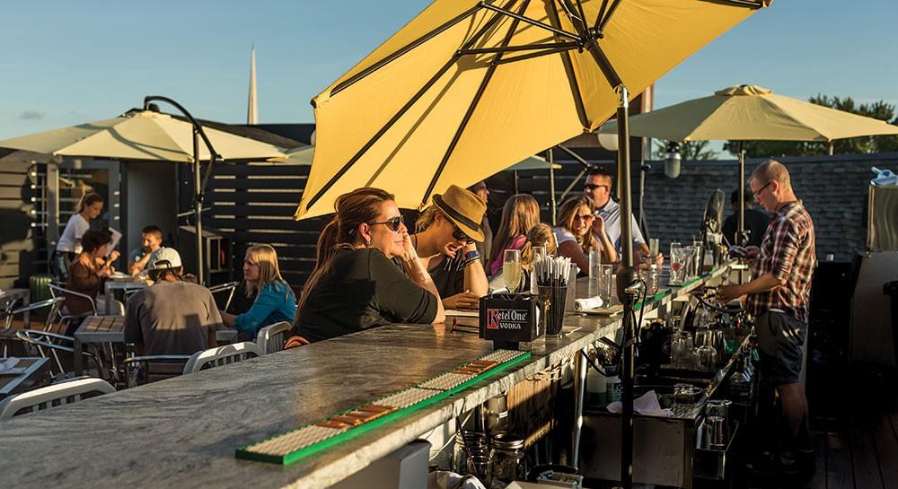 Derek Williams tending bar on the rooftop deck at Redwood - FRANCO VOGT