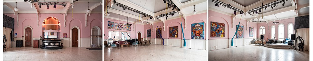 Once the center of Odd Fellows revelry, Bickman now utilizes the building's third floor ballroom as a community event space. Musical performances, aerial yoga and her Mural Arts Program are regularly held in the 24-foot-high room. Her 4' by 6' Laughing at Death hangs above the mirror. Hanging amongst the arches, her 5' by 7' series contemplating spiritual themes was completed during her time in Florida. From left to right is Dancing Shiva, Vajrayogini, Taming the Mind, Christ Buddha, and Green Tara. - PHOTOS BY DEBORAH DEGRAFFENREID