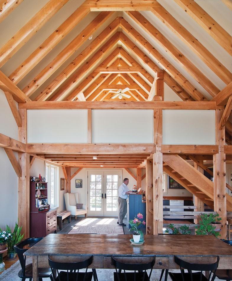 View across dining room table to - kitchen nestled under loft bedroom. - DEBORAH DEGRAFFENREID
