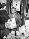 1935: Jesse Owens brings Christmas gift baskets to needy families.