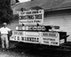1962: A man stands next to an old bobsled, which now serves as a stand for a Christmas tree farm, at the county fair.