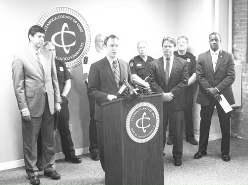 Ed FitzGerald, surrounded by county officials and safety leaders from various suburbs, announces a stricter approach to heroin investigations.
