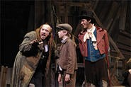 Fagin (George Roth) teaches Oliver (Lincoln Sandham) as the Dodger (Chris McCarrell) watches.