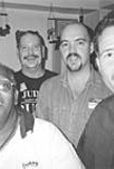 Greg Ammell (second from left), laughing with friends      at his Lakewood home.