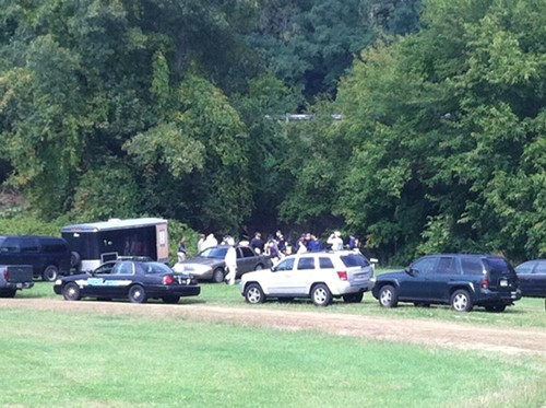 Investigators congregate at the treeline at Clark Fields Oct. 2.