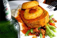 Juicy meatloaf, doused in tangy gravy and resting on a bed of spuds, satisfies manly appetites. - WALTER NOVAK